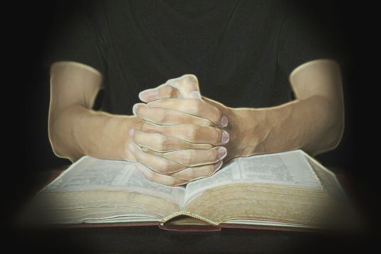 Closeup of hands in praying position with a bible